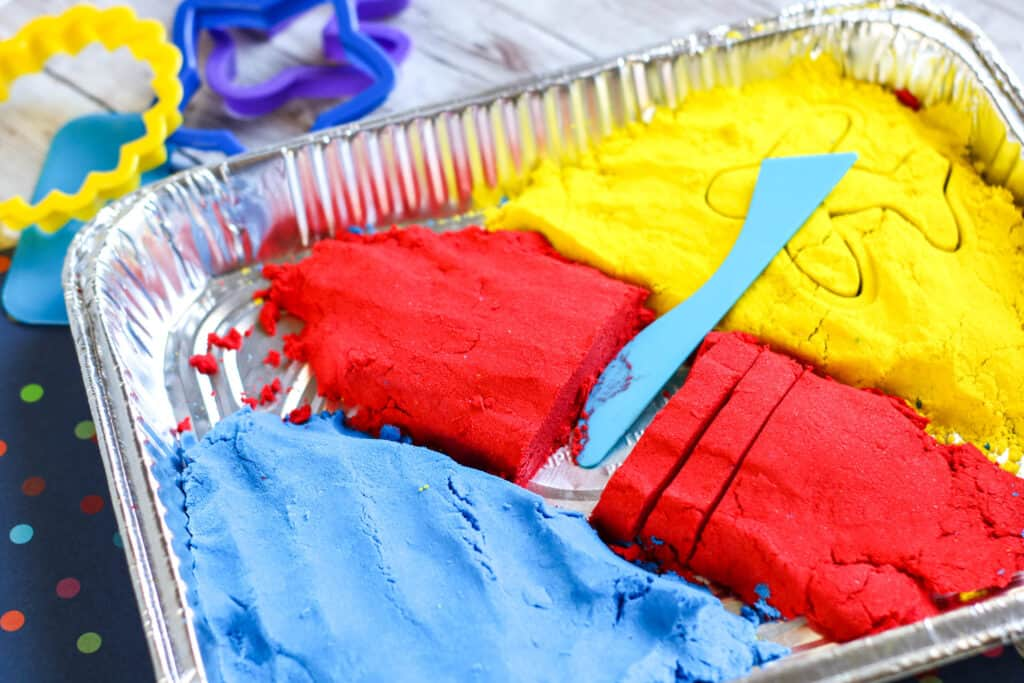 Blue, red, and yellow Homemade Kinetic Sand Recipe with cookie cutters and other play things for the sand.