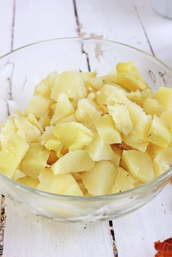 A bowl of cooked, peeled, and cut potatoes.