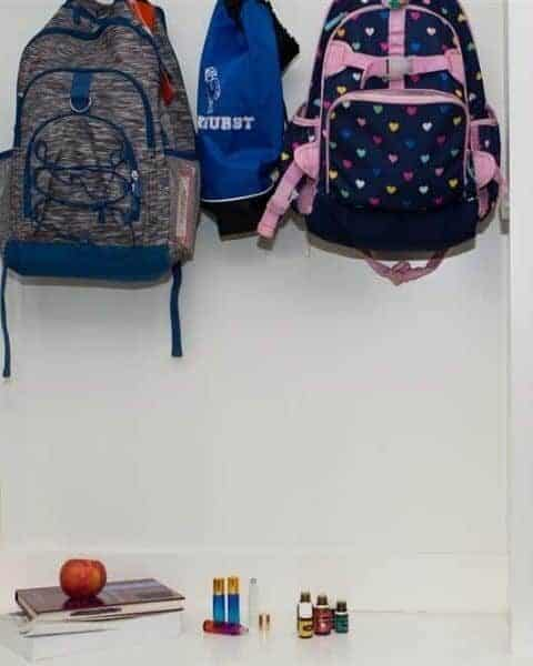 backpacks hanging in a hallway with several books, an apple and bottles of essential oils below them on a table.