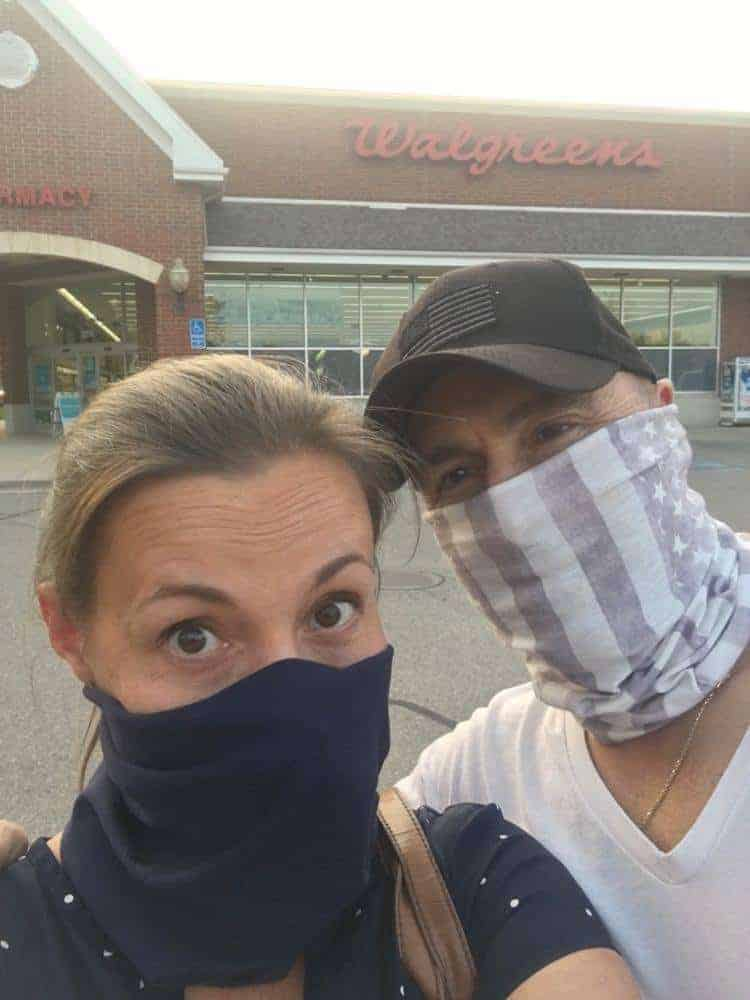 Man and woman wearing face masks and shopping outside of Walgreens.