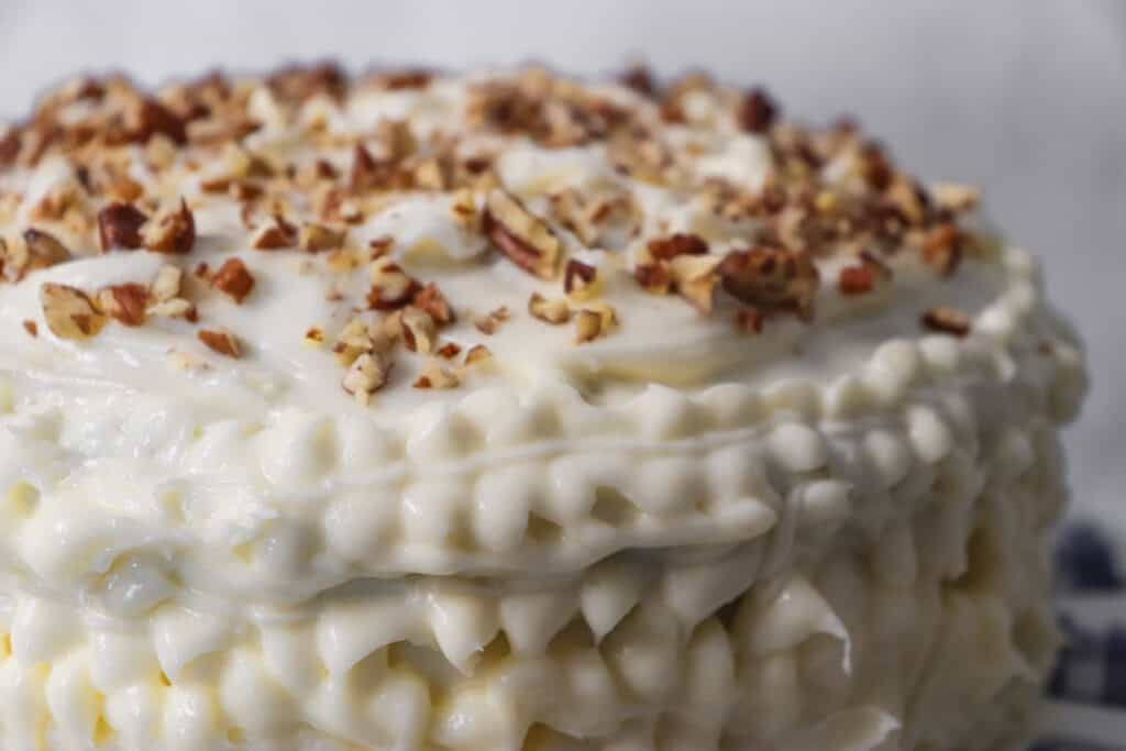 close up picture of a frosted zucchini cake with chopped pecans on top.