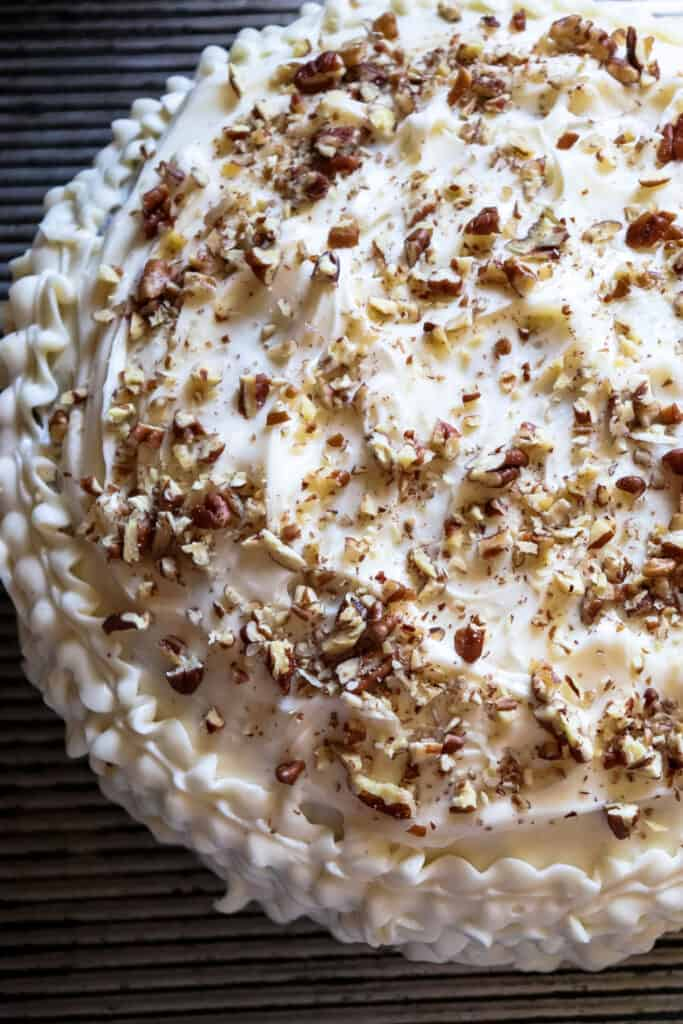 frosted zucchini cake with chopped pecans on top.