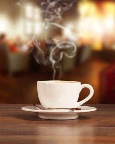 a cup of steamy coffee sitting on a wooden table.