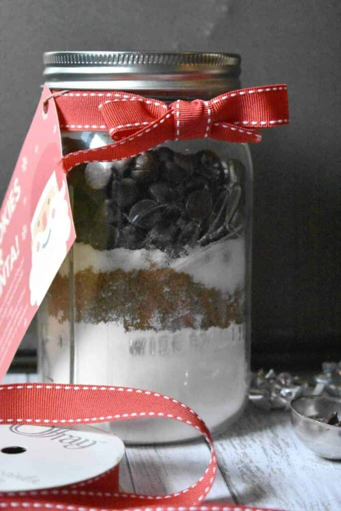 Jar with flour, sugar, and chocolate chips wrapped in a red Christmas ribbon.