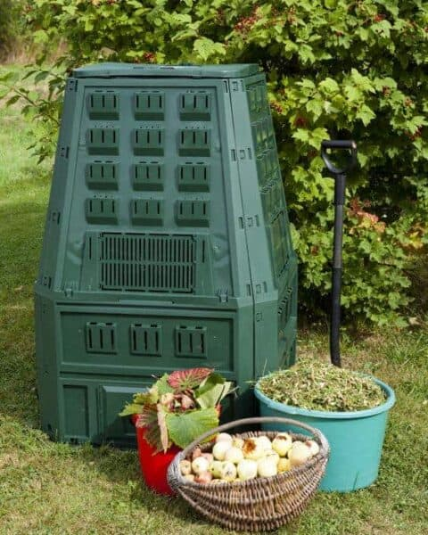 compost bin with buckets of food scraps sitting nearby