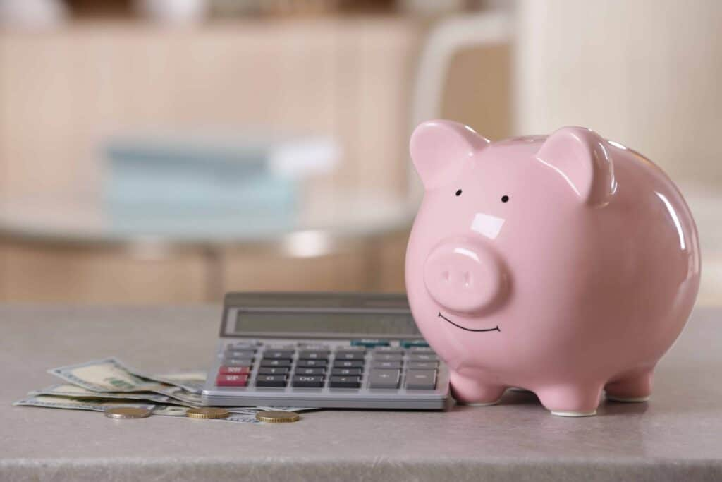 pink ceramic piggy bank sitting near a calculator and money. Saving power concept.