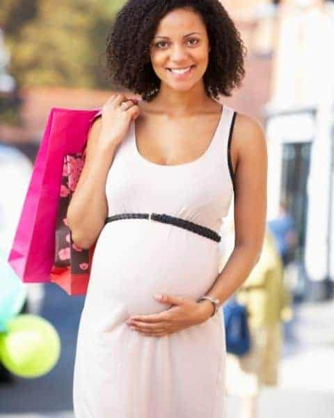 A young mother who is cradling her pregnant belly while carrying pink shopping bags.