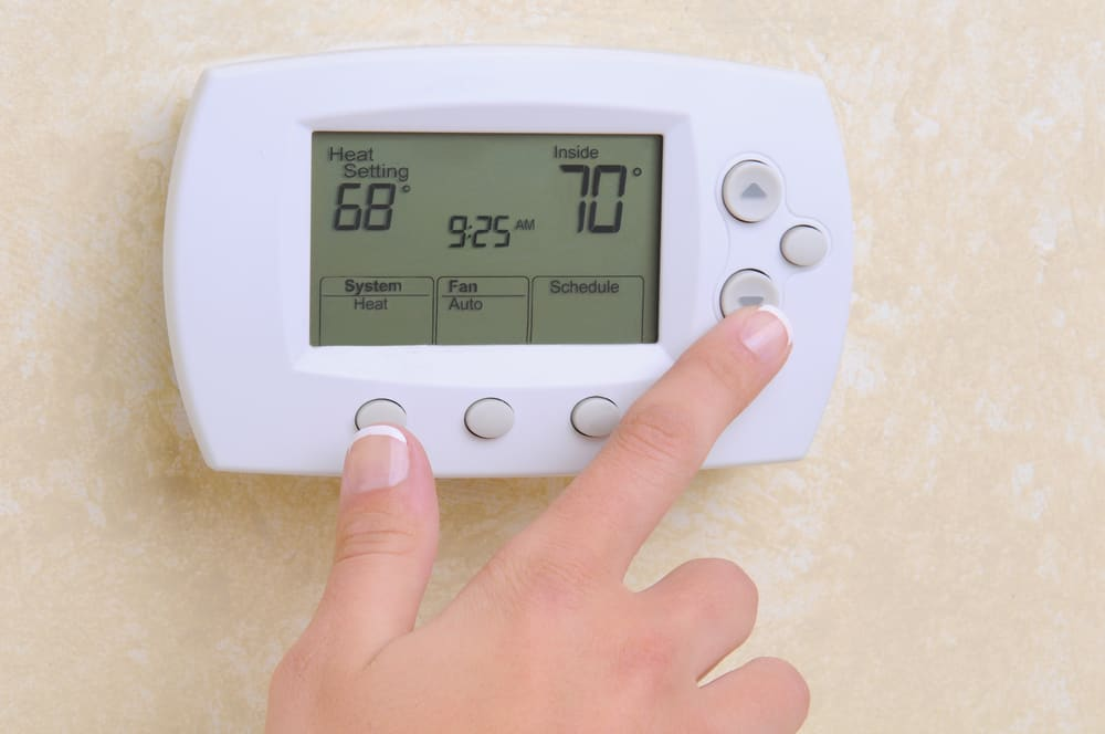 Woman adjusting the temperature setting on a programmable thermostat.