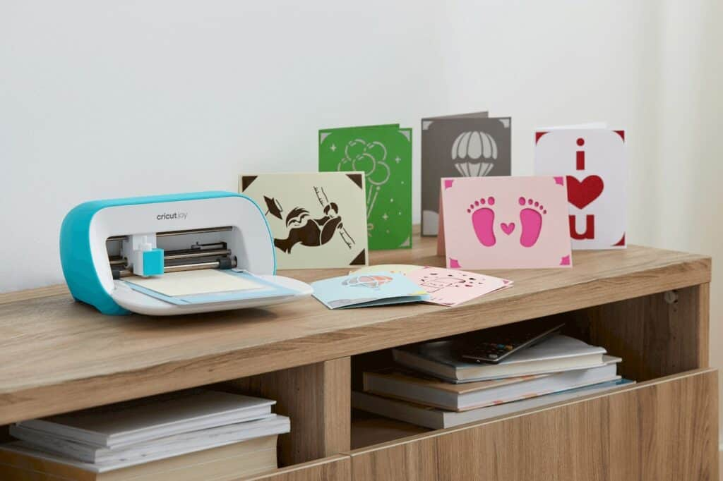 a Cricut machine sitting next to several homemade cards.