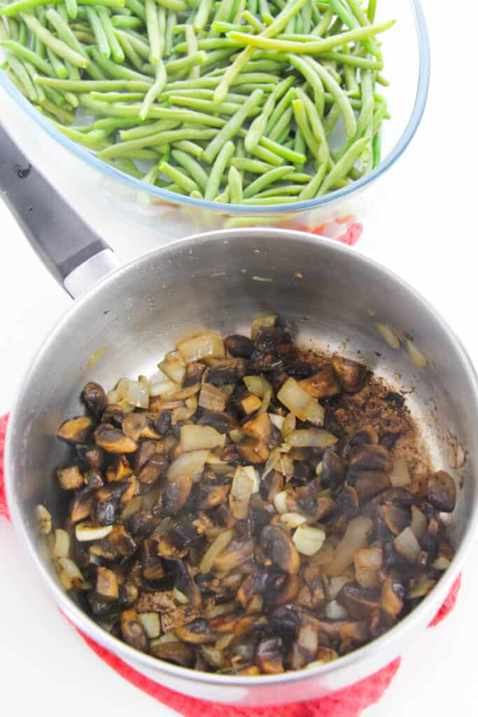 onions and mushrooms sauteed in a pan sitting near a bowl of fresh green beans