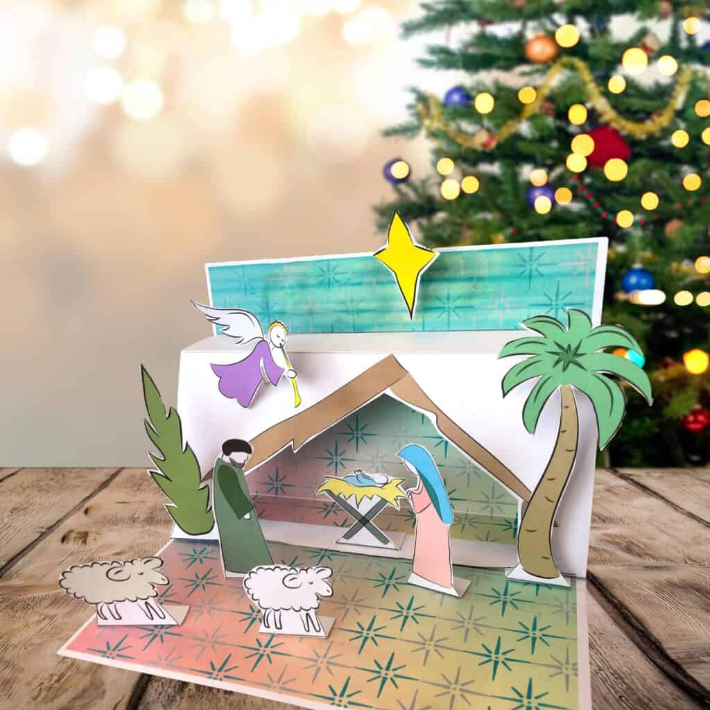 completed nativity scene on a table in front of a christmas tree