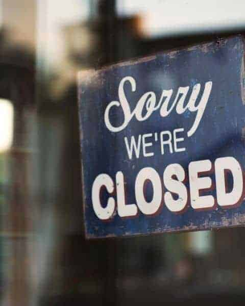 sign hanging in a door saying sorry we're closed
