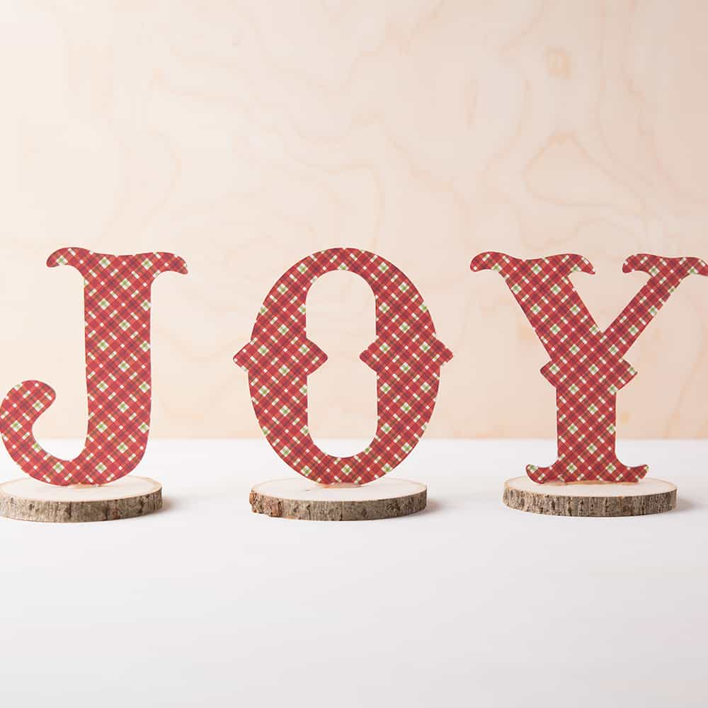 JOY sign on wood with red decorative plaid.