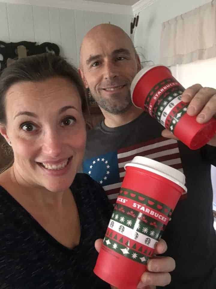 A happy couple with Starbucks coffee cups.