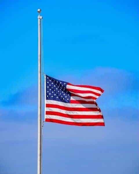 A United States flag at half massed on a flag pole.