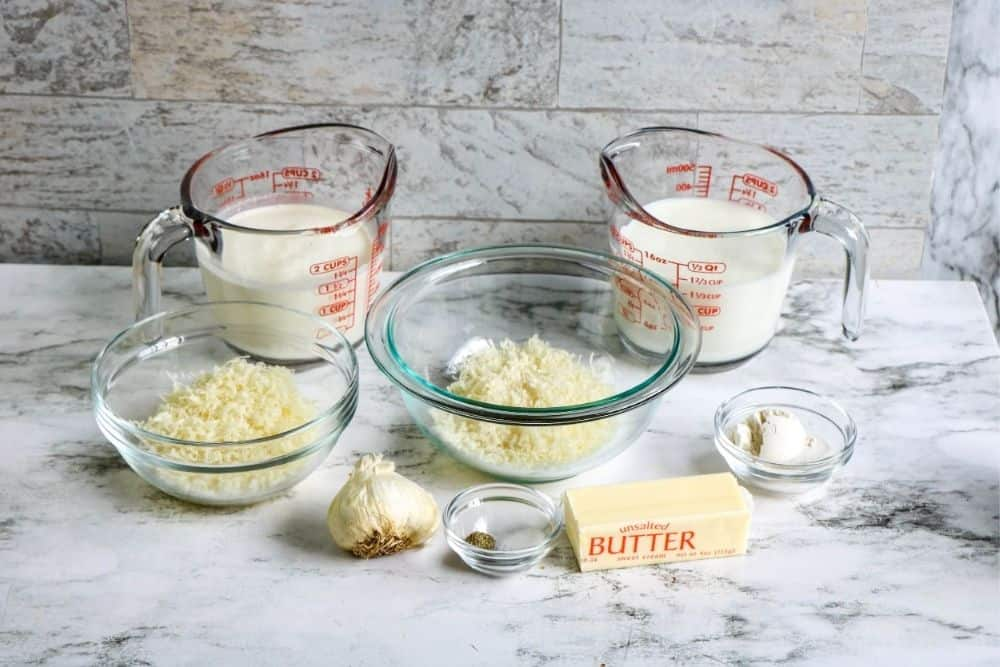 The ingredients to make alfredo sauce sitting on a countertop, including butter, garlic, cheeses, milk and heavy cream.