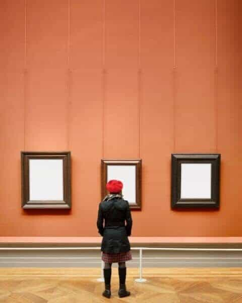 A woman looking at three framed pieces of art with blank white canvases.