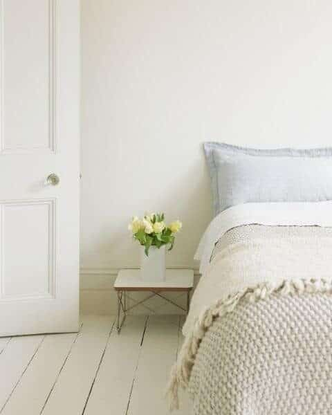 A clean bedroom with fresh flowers next to the bed stand.