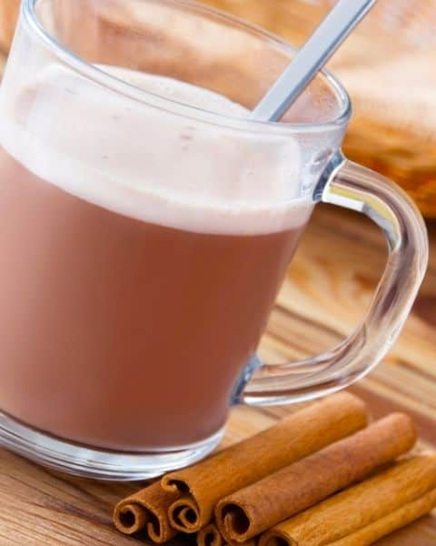 A frothy cup of vanilla chai latte with cinnamon sticks next to the cup.
