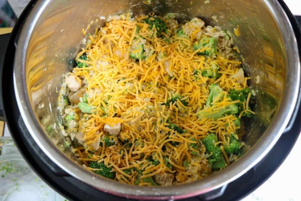 broccoli, chicken and rice covered in shredded cheese cooking inside a pressure cooker.
