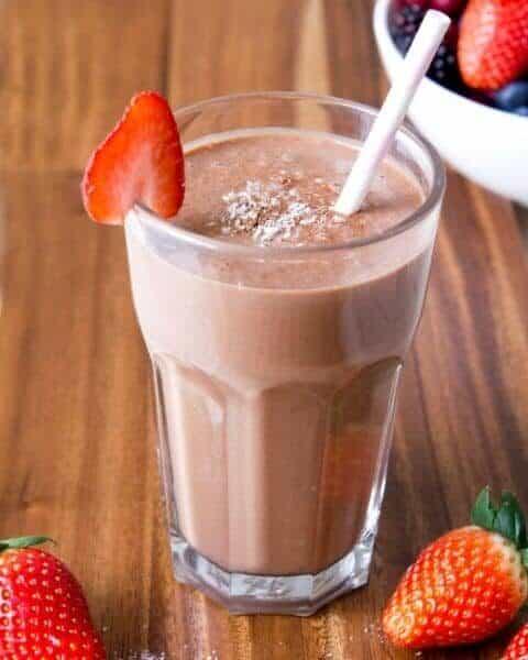 Chocolate strawberry smoothie with straw.