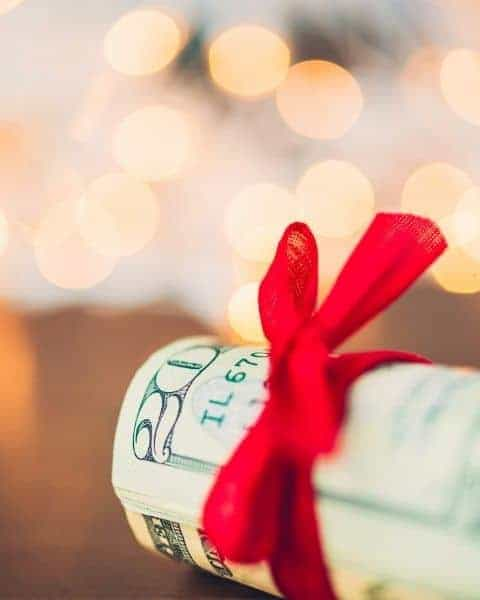 a roll of cash wrapped in a red ribbon.