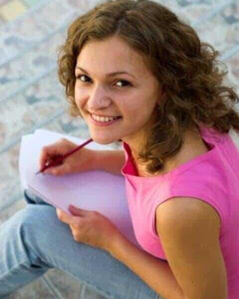 A young woman in a pink shirt writing in a notebook.
