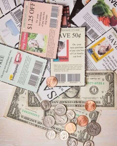 A variety of coupons and cash, including bills and coins, piled on top of each other.