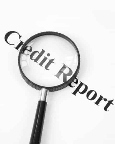 Credit report with magnifying glass on top of words.