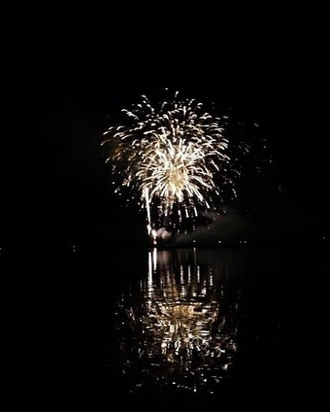 Fireworks going off over the water.