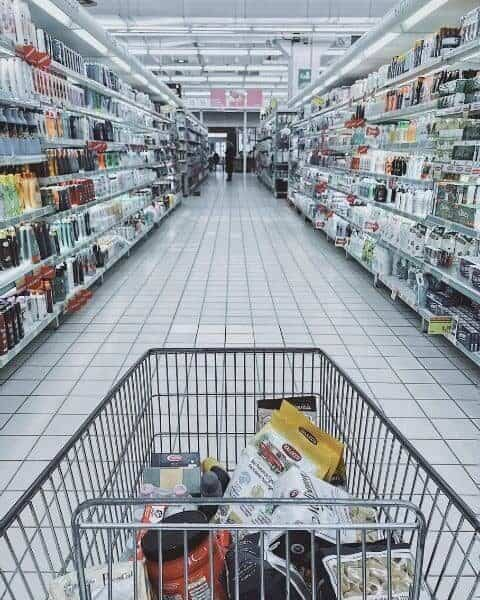 A filled cart in the middle isle of the grocery store.