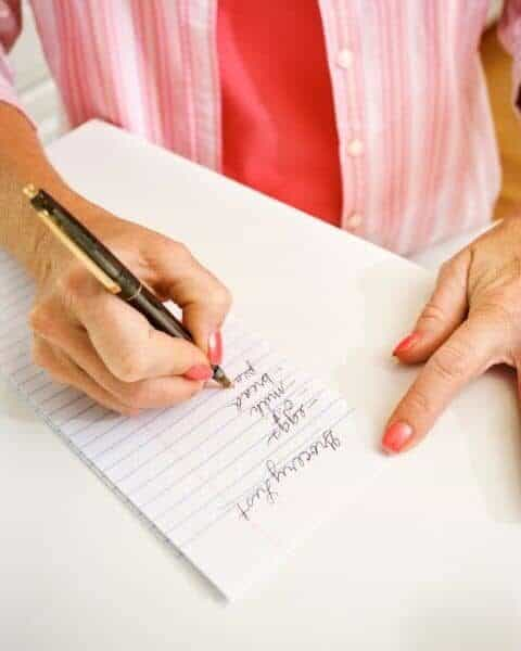 A woman making a list of groceries.