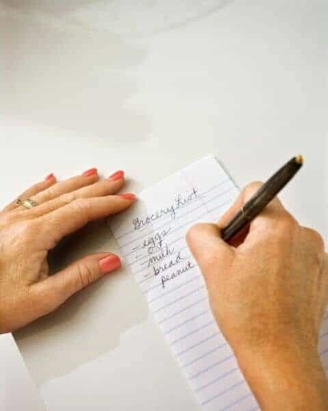 A woman making a grocery list, including eggs, milk, bread, and more food items on the list.