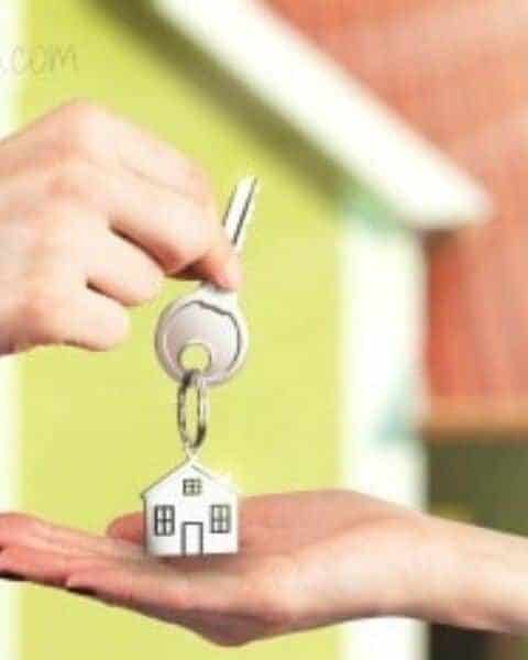 One person handing a key with a house keychain to another person after purchasing a home.