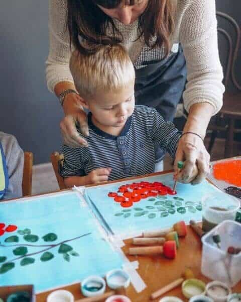 A woman helping a small boy with painting.