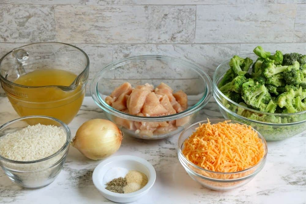 Bowls of chicken and broccoli ingredients - broccoli, cheese, spices, onion, rice, chicken and broth sitting on a countertop.