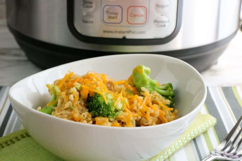 A white bowl full of chicken and broccoli casserole sitting in front of an Instant Pot