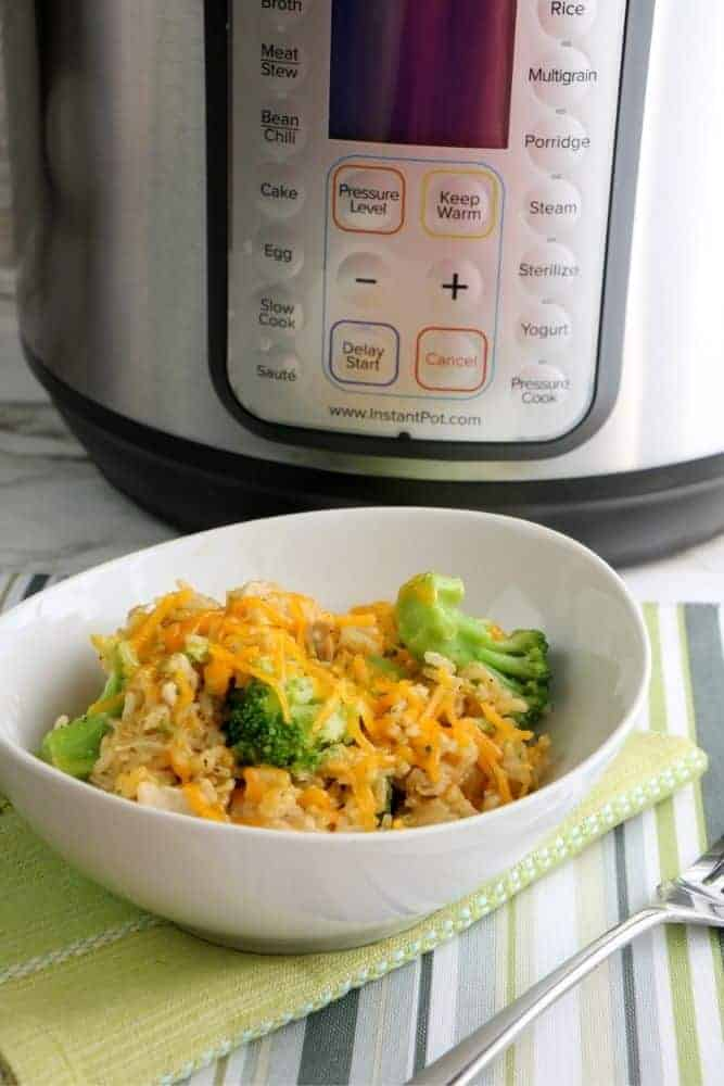 A close up of a bowl filled with cheesy chicken broccoli rice sitting in front of an Instant Pot