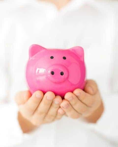 A small child holding a very bright pink piggy bank in her hands.