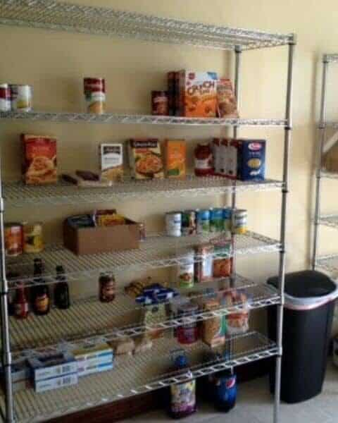 A variety of canned and boxed foods on shelves in the garage for food storage.