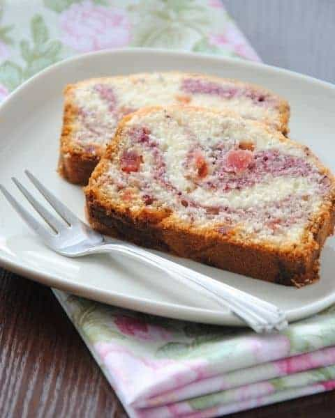 Freshly baked Copycat Starbucks Raspberry Swirl Pound Cake Recipe slices on a white plate and silver fork.