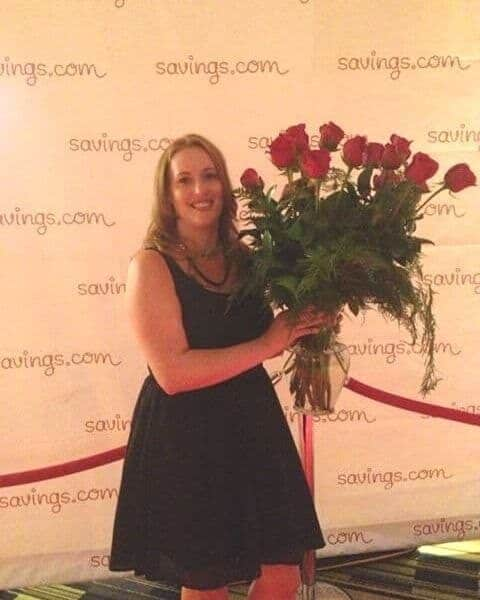 A smiling woman holding a beautiful bouquet of red roses.