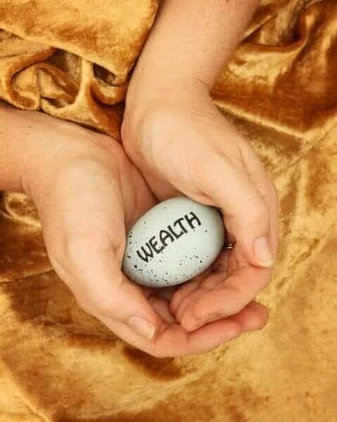 """A woman holding an egg in her hands with the words """"wealth"""" on the egg."""