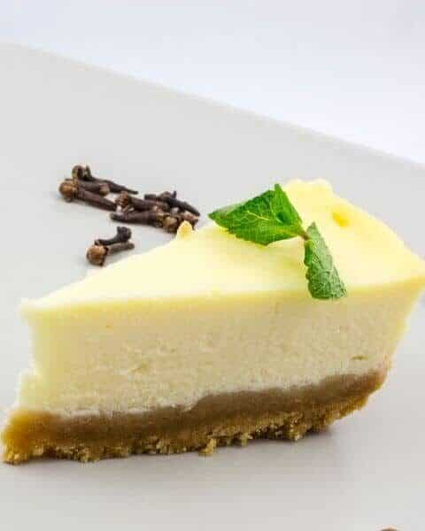 A slice of white chocolate cheesecake recipe with a small green mint on top.