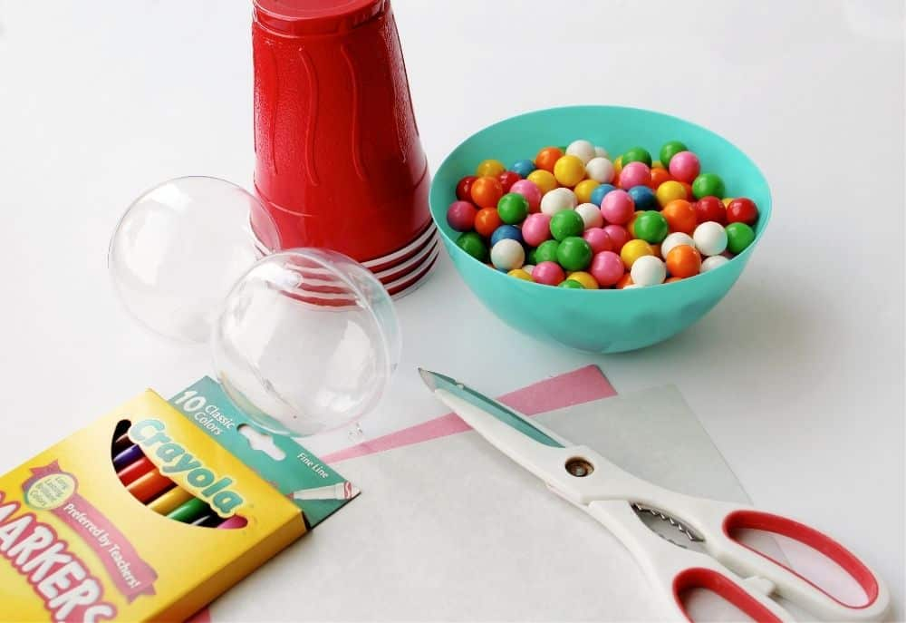 All of the items needed to make mini bubble gum machines: an empty clear ornament, red plastic cups, a bowl full of colored mini gum balls, scissors, construction paper and markers.