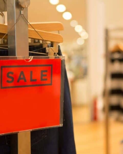 A red sale sign on a clothes wrack at the department store.