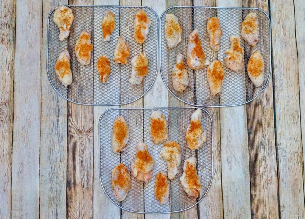 Seasoned chicken wings on three air fryer racks.