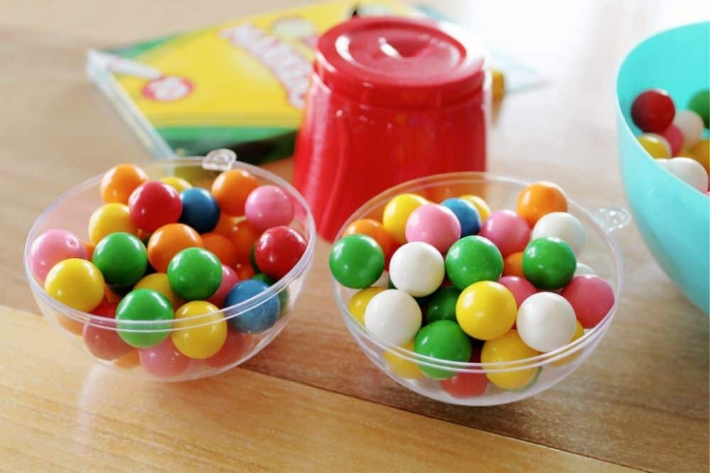 An opened plastic clear ornament sitting on a table filled with brightly colored gum balls.