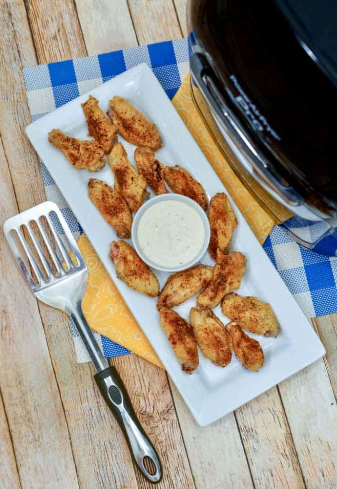 cooked chicken wings sitting on a plate with a cup of ranch dressing , next to an Air Fryer.
