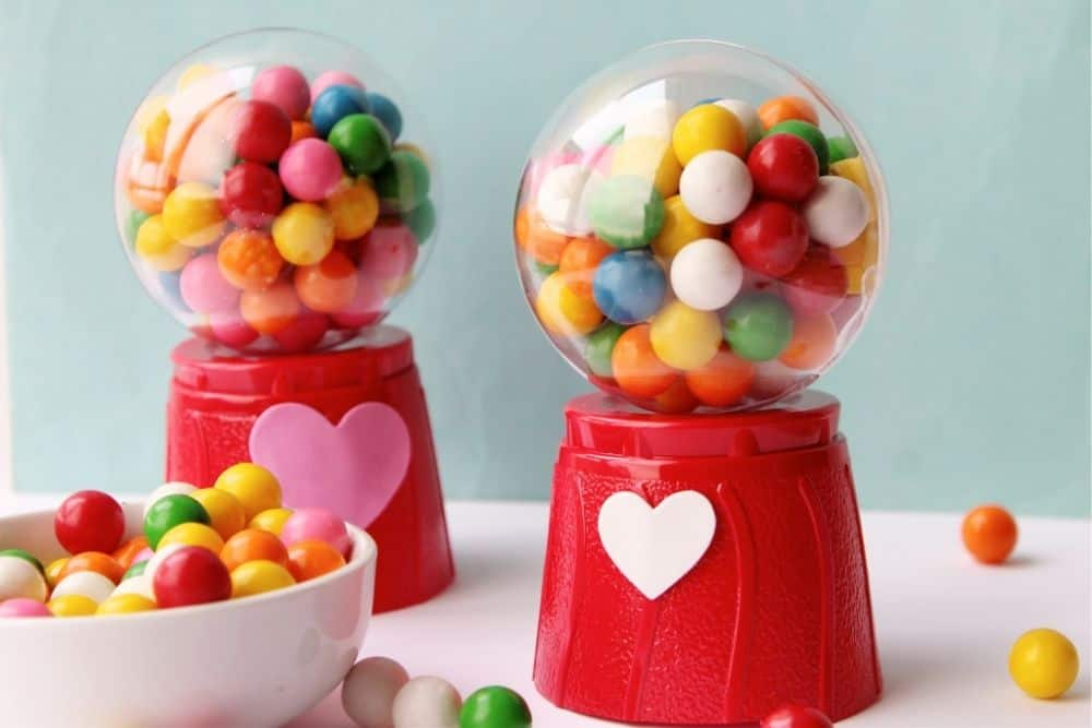 A white ceramic bowl filled with red, green, pink, orange, white and yellow mini gumballs sitting on a table next to two crafted mini gum ball machines.
